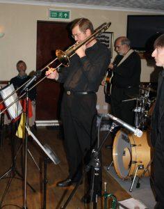 Bill Todd takes a solo for Phoenix Dixieland Jazz Band at Farnborough Jazz Club on 23rd October 2015. (LtoR) Bill Todd (trombone), John Stuart (banjo) and Paul Higgs (trumpet). Photo by Mike Witt.