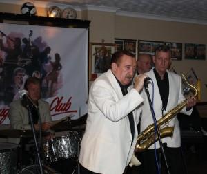 Denny Ilett sings, seen here with John Tyson (drums), Al Nichols (tenor sax) and Tony Pitt (banjo) with 'Tony Pitt's All Stars' at Farnborough Jazz Club (Kent) on 9th October 2015. Photo by Mike Witt.