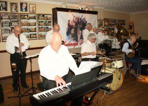 Yerba Buena Celebration Jazz Band at Farnborough Jazz Club (Kent) on 3rd June 2016. (LtoR) Brian White (clarinet), Hugh Crozier (piano), Mike Barry (2nd trumpet &vocals), Pete Lay (drums), Dave Rance (1st trumpet &vocals), George 'Kid' Tidiman (trombone), John Arthy (tuba) & Nick Singer (banjo &vocals). Photo by Mike Witt.